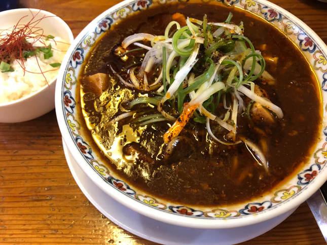 濃厚な茶色のスープが特徴のラーメンとご飯のセット
