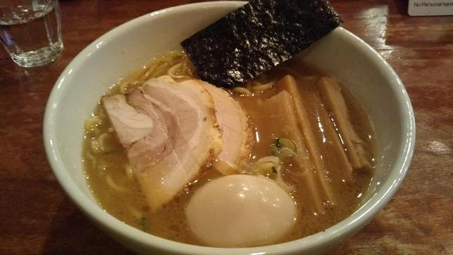 濁った茶色のスープに麺とチャーシューと煮卵と海苔とメンマが入ったラーメン