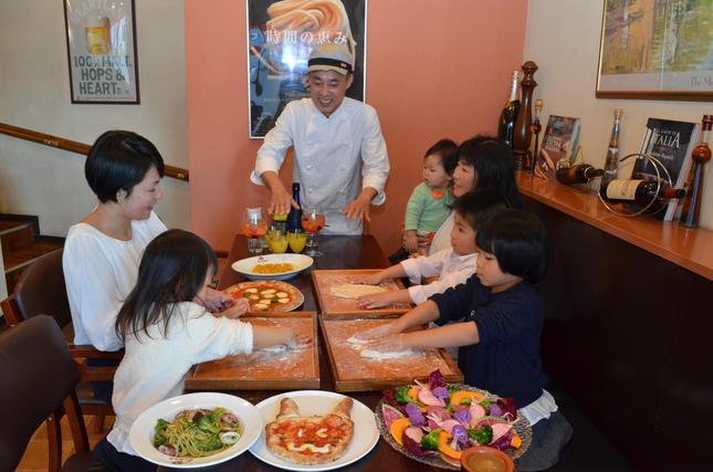 友達同士のパーティーで楽しそうにピザをこねる子供と大人達